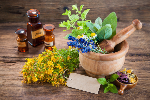 Mortar with fresh herbs and empty tag on wooden background